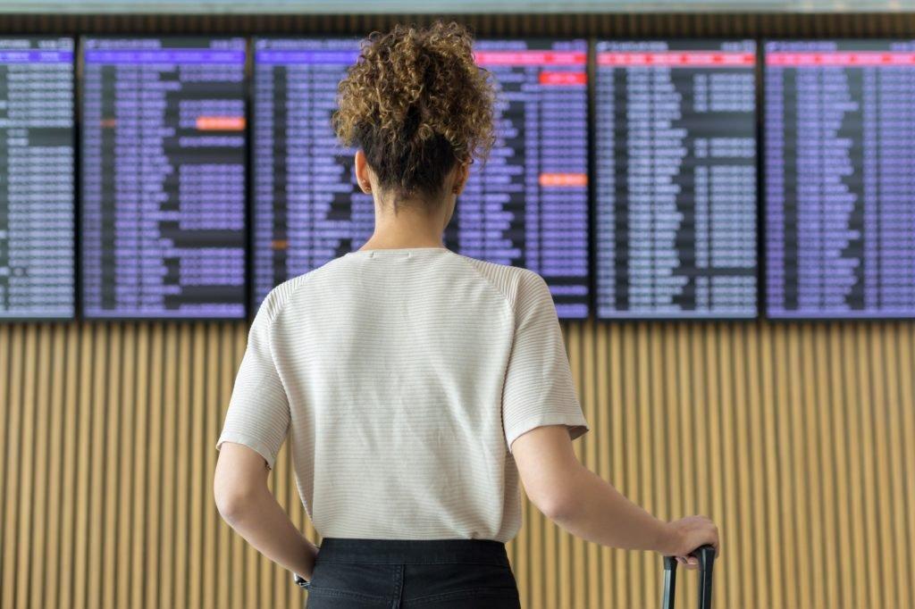 Mulher checando os horários de voos no aeroporto